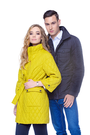 Fashion shot. Couple of young people in winter clothes posing at studio. Autumn and winter clothes. Stock Photo