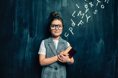 A portrait of a cute girl standing with a book over a blackboard. School, education. Stock Photo