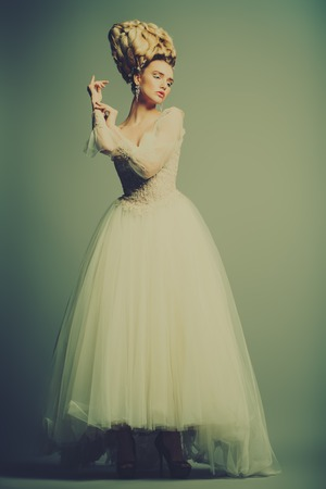 A full length portrait of a cold beautiful lady wearing a fluffy dress and posing in the studio over the grey background. Beauty,cosmetics, hairstyle, fashion.