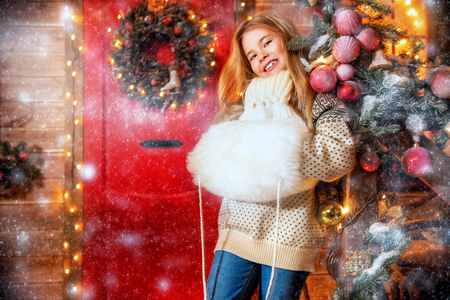 A portrait of a pretty girl standing on the porch of a house decorated for Christmas and New Year. Merry Christmas, happy New Year. Miracle time. Standard-Bild - 112449192