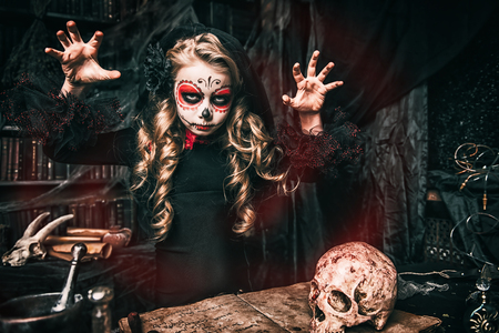 Halloween party. A child girl in a costume of Calavera Catrina in the scenery of the witch's lair. Standard-Bild - 112590392