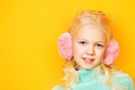 A cute cheerful girl in warm pink headphones is posing over the yellow background. Beauty, fashion for kids.