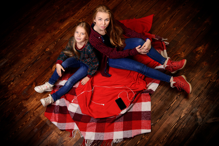 Family concept. Two cute girls, older and younger sister sitting together on a floor. Childrens fashion.