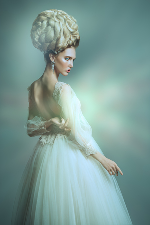 A portrait of a cold beautiful lady wearing a fluffy dress and posing in the studio over the grey background. Beauty,cosmetics, hairstyle, fashion.