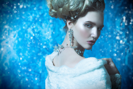 A close up portrait of a cold beautiful lady posing in the studio over the blue background. Beauty,cosmetics, hairstyle.