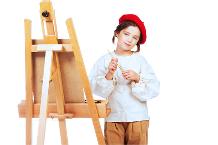 A portrait of a positive girl painting a picture. Creativity, artist. Stock Photo