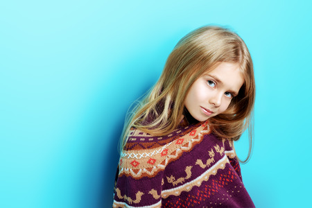 Kids fashion. Portrait of a cute 7 year old girl wearing knitted clothes posing over bright blue background. Autumn, winter fashion. Happy child girl. 写真素材