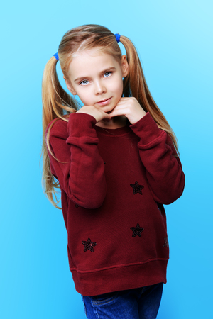 Kid's fashion. Portrait of a cute 7 year old girl wearing knitted clothes posing over bright blue background. Autumn, winter fashion. Happy child girl. 写真素材