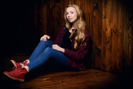Cute  teenager girl is sitting in casual clothes on a floor. Stock Photo