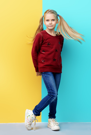 Kids fashion. Full length portrait of a cute 7 year old girl wearing knitted clothes posing over bright yellow and blue background. Autumn, winter fashion. Happy child girl.