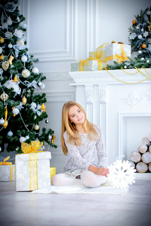 Pretty nine year old girl opens a gift box and surprises. Luxurious apartments decorated for Christmas. Merry Christmas and Happy New Year. Фото со стока