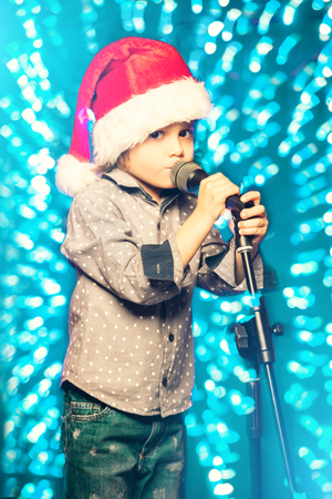 A young boy is singing a song. Merry Christmas and Happy New Year.