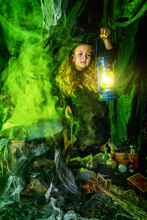 Happy Halloween. Cute child girl in witch costume is in a witch's lair. Cute cheerful little witch cooks a magic potion. Standard-Bild