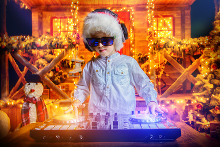 Emotional little boy-DJ is having a party near the house of Santa Claus decorated with lights. Christmas party concept. Standard-Bild - 112785461