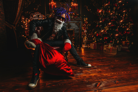 Ð¡heerful punk Santa with a bag of gifts in his hands  in luxurious apartments decorated for Christmas. Bad Santa concept.