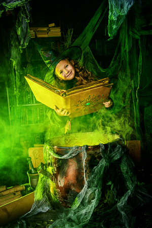 Happy Halloween. Cute child girl in witch costume is in a witch's lair. Cute cheerful little witch with a book of spells cooks a magic potion. Standard-Bild