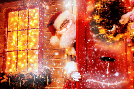 Portrait of a fairytale Santa Claus which looks out from behind the door onto the porch.  Beautiful house decorated for Christmas. Time of miracles. Christmas concept. Stock Photo