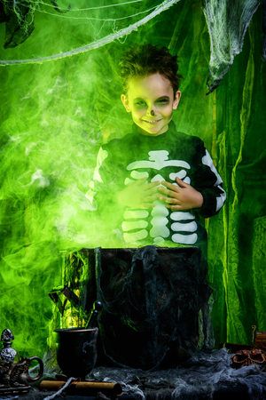 Happy Halloween. Funny child boy in a costume of skeleton cooks a magic potion in a witch's lair. Standard-Bild - 112785569