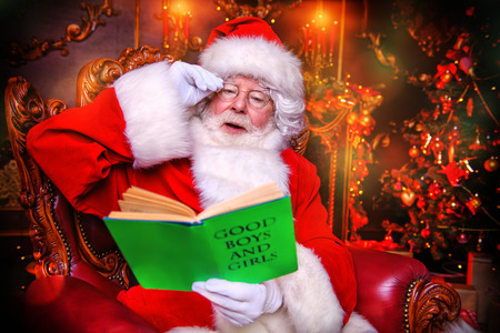 A portrait of Santa Claus sitting at his home with book of good boys and girls. Miracle time. Christmas, New Year. Imagens