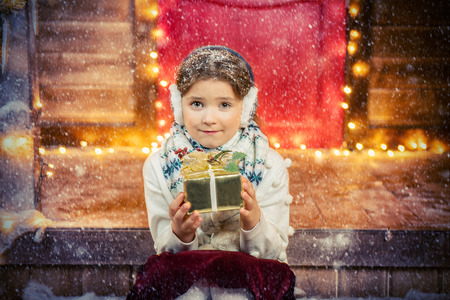A cute girl is sitting on the porch of the house decorated for Christmas and holding a gift box. Merry Christmas, Happy New Year. Miracle time.