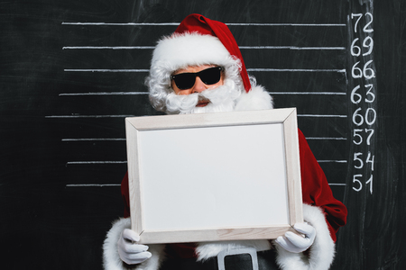 A portrait of Santa Claus in sunglasses holding a plate. Merry Christmas and Happy New Year! Stock Photo - 112812055