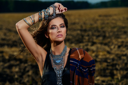 Fashion female model posing in a field. Contemporary bohemian style. Stock Photo