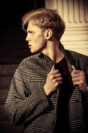 Portrait of a handsome young man with blond hair wearing in a plaid coat, standing on a city street. Mens beauty and health. Beauty, city fashion.