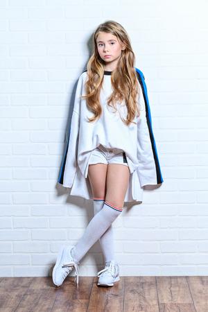 Pełnej długości portret słodkiej emocjonalnej dziewczyny pozującej na białej ścianie z cegieł. Uroda, moda dla dzieci i młodzieży.