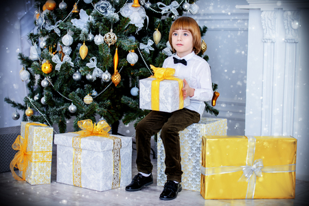 Cute five-year-old boy sits in a beautiful room near a Christmas tree with gift box. Luxurious apartments decorated for Christmas. Merry Christmas and Happy New Year.