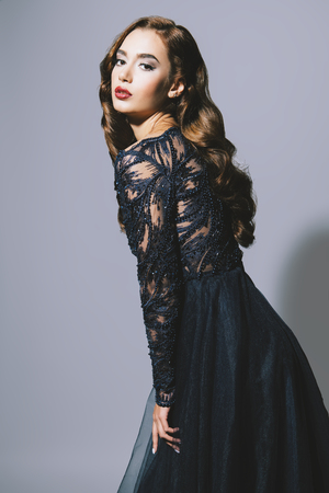A portrait of a beautiful dark-haired lady in the studio. Evening dress. Fashion, beauty. Stock Photo