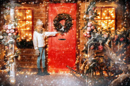 A pretty girl is on the porch next to the door of the house decorated for Christmas. Winter fashion for kids. Merry Christmas and Happy New Year. Stock Photo
