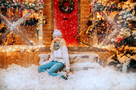 A pretty girl is sitting on the porch in front of the house decorated for Christmas. Winter fashion for kids. Merry Christmas and Happy New Year.