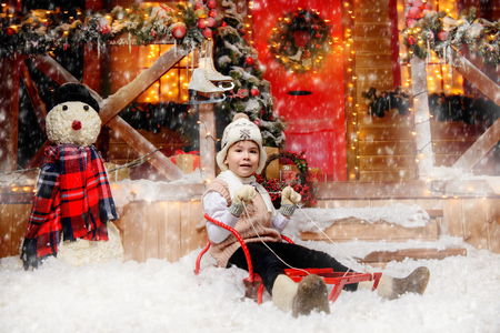 A cute little boy in winter clothes and a hat is sitting on the sledge in front the magic house of Santa Claus. Miracle time. Merry Christmas and Happy New Year. Standard-Bild - 113363169