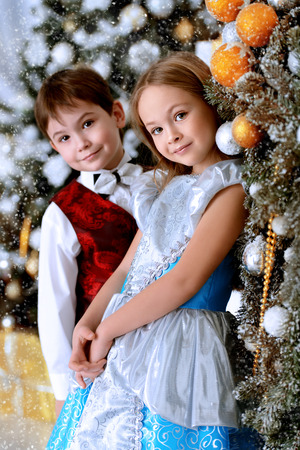 Cute brother and sister are posing near a Christmas tree at home decorated for Christmas. Merry Christmas and Happy New Year. Stock Photo