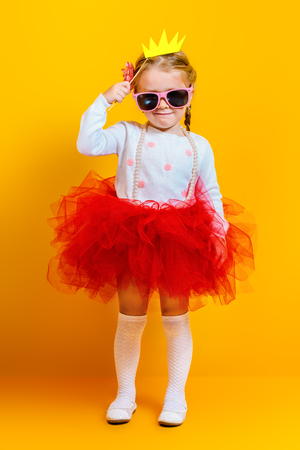 A portrait of a bright young pretty girl in skirt and sunglasses. Summer bright fashion for kids. Stock fotó