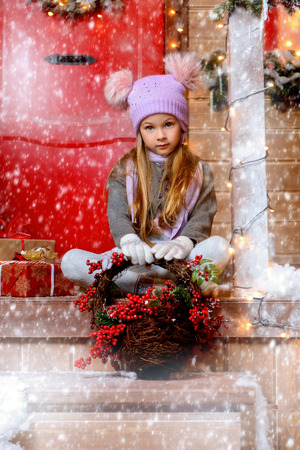 A pretty little girl is sitting and is holding a basket of Rowan berries in front of the porch of a house decorated for Christmas. Merry Christmas and Happy New Year.