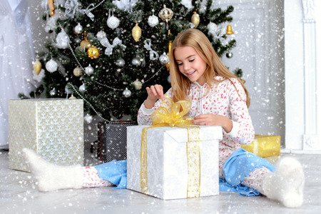 Pretty smiling girl is sitting on floor and look at a gift in a Christmas room. Merry Christmas and Happy New Year.