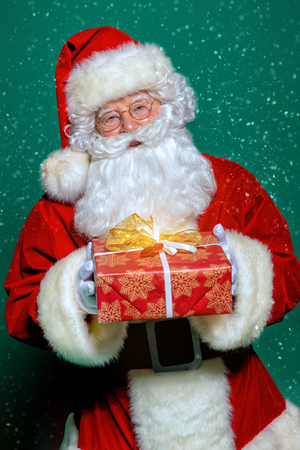 A portrait of Santa Claus holding a gift box. Merry Christmas and Happy New Year!