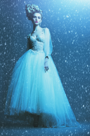A full length portrait of a cold beautiful lady wearing a fluffy dress and posing in the studio over the blue background. Beauty,cosmetics, hairstyle, fashion.