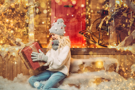 A happy girl is sitting on the porch in front of the house decorated for Christmas and holding a gift. Winter fashion for kids. Merry Christmas and Happy New Year.