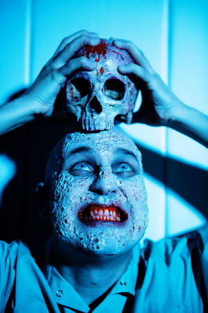 A portrait of a sick scientist after a failed experiment in the blue light holding a skull. desperation, hopelessness. Horror, halloween. Banco de Imagens