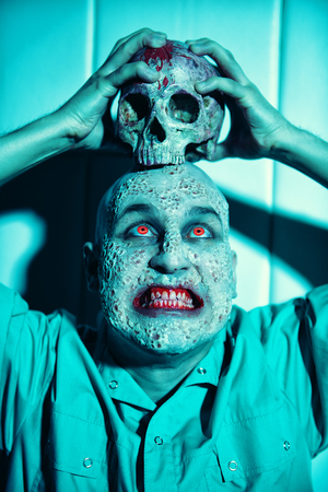 A portrait of a sick scientist after a failed experiment in the blue light holding a skull. desperation, hopelessness. Horror, halloween. Stok Fotoğraf