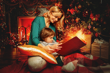 Mother and her son are reading a book at home decorated for Christmas. Family miracle time. Merry Christmas and Happy New Year.