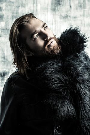 Fashion shot of a stylish brutal bearded man wearing fur coat. Studio shot over grunge background. Stock Photo