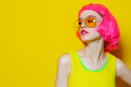 Close-up portrait of a trendy girl with pink hair wearing yellow sunglasses over yellow background. Beauty, fashion concept. Make-up and cosmetics. Studio shot.