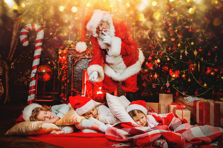 Santa Claus is putting gifts while children are sleeping at home. Merry Christmas and Happy New Year. Miracle time.