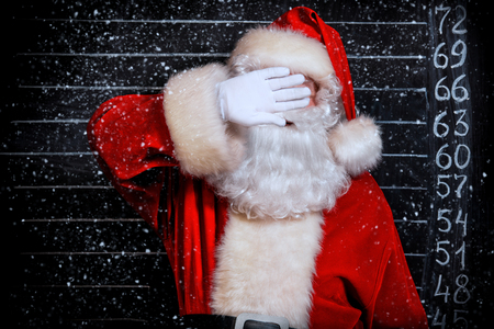 A portrait of Santa Claus covering his face. Merry Christmas and Happy New Year!