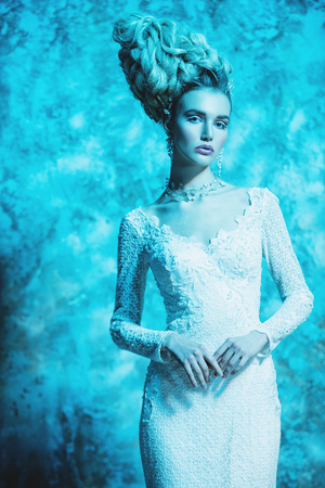 A portrait of a cold beautiful lady wearing a tight dress. The snow Queen. Beauty,cosmetics, hairstyle, fashion. Stock Photo - 113544245
