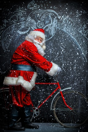 A portrait of Santa Claus with a bike. Merry Christmas and Happy New Year! Standard-Bild