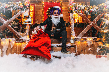 Cool punk Santa is sitting around near his house with a bag of gifts in his hands. Stock Photo